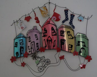 Hand painted wall sculpture, with washing line and girl on a bicycle.