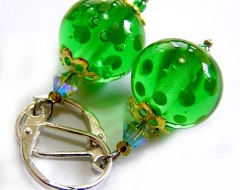 A pair of handmade lampwork earrings in green and sterling silver