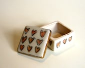 tiny porcelain box with pink underglaze heart pattern and 22k bright gold luster