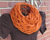 Arm knit chunky infinity cowl in soft wool blend yarn in burnt pumpkin