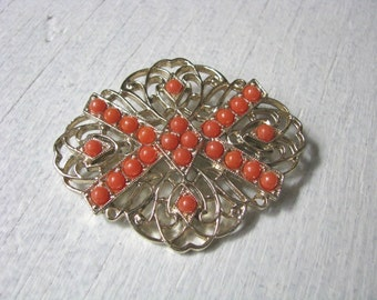 Dramatic gold tone filigree brooch pin with orange stone accents. Tangerine by Sarah Coventry