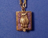 Owl Peace Book, purple and gold, holding 14 words for Peace from around the world