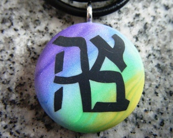Ahava Hebrew Love hand carved on a polymer clay multi color clay background. Pendant comes with a FREE necklace