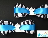 Teal, black, and white zebra print hair bows with ghosts. Portion of sale goes to charity.