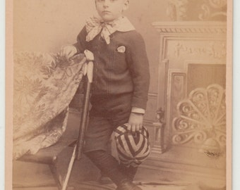 Vintage/Antique cabinet photo of a boy in very nice outfit holding a stripe hat