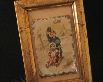 Small Lemon Gilt Framed Christmas Ornament of an 1898 Card Showing Sledding Children