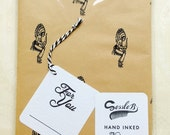 Retro hand stamped wrapping paper and gift tag. Vintage 1950's red indian stamp. Black ink on brown paper.
