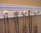 Jewelry organizer This shabby chic flowered necklace hanger has 9 decorative cabinet knobs off white w/white embossed background 26 inches