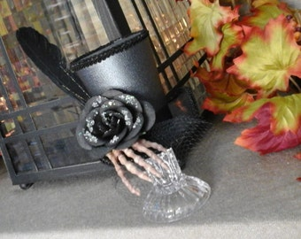 Black mini top hat with skeleton hand and black glitter flower, this piece is attached to a glass stand
