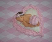 Baby girl on heart pillow