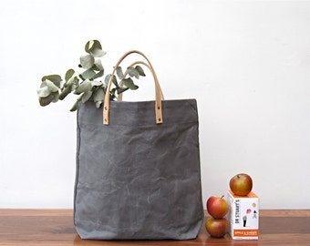 Sale now 25% 0ff. Grey shopper. A washed canvas carrier bag with natural leather handles and brass details.