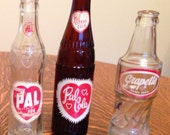 Lot of 3 Glass Soda Pop Bottles -Pal Ade, Pal Citrus Cola, and Grapette -Brown and Clear Heart Painted Embossed Valentine Logo Red and White
