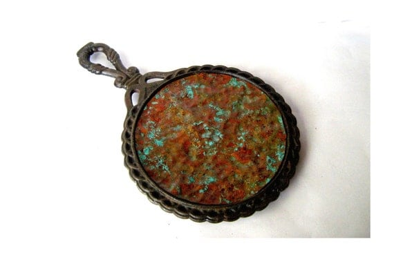 Vintage rustic cast iron pot stand. Rusty iron trivet with a verdigris copper surface. Country farmhouse chic.