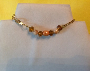 An Anklet with gold tone colors.