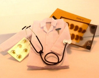Doctor's office. Lab coat, x-rays with envelope, stethoscope, container of pills dollhouse miniature
