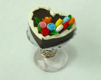 Chocolate heart cake with roses and on a decorative cake stand.