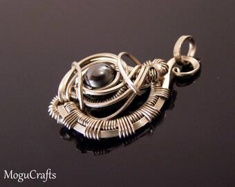 Futuristic, three-dimensional wire wrapped  pendant design adorned with a hematite