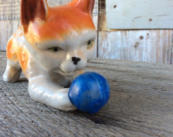 Charming ceramic orange cat playing with blue ball
