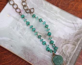 Pressed glass flower and Budda symbol pendant