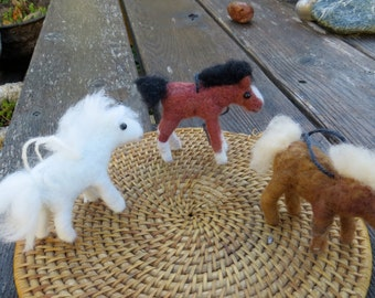 Two needle felted ponies and one needle felted foal. Just plain adorable