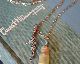 In a Bottle.  Vintage watchmakers vial and seahorse mixed media charm necklace. Ocean themed necklace