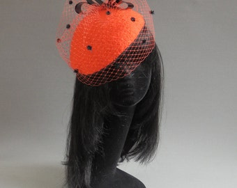 Between red and orange bouclé fabric is used to cover this buckram percer hat in Duchess of Cambridge style with two birdcage veils on comb