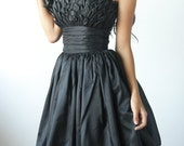 Cocktail dress or prom frock made from taffeta with knee length skirt and petal detaIl