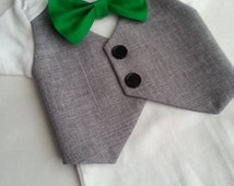 Baby Boy Bodysuit With A Grey Vest Attached And A Green Bow tie.