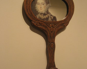 Mirror, Mirror. Altered vintage wood hand mirror with Elizabethan image and hardware, hangs on wall