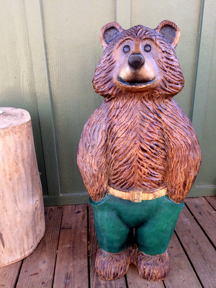 Foot brown bear with trousers chainsaw wood sculpture