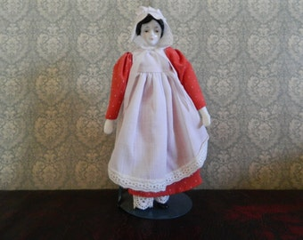 Porcelain Doll Wearing Red Dress And Bonnet With Stand