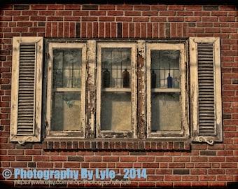 Fine art photograph of rustic outdoor window shutters, wooden shutters, distressed wood, peeled paint, window dressing, bottles, brick wall