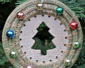 Festive hand-stitched and coiled pine needle Christmas ornament with colorful round beads and Christmas tree cutout ceramic center.