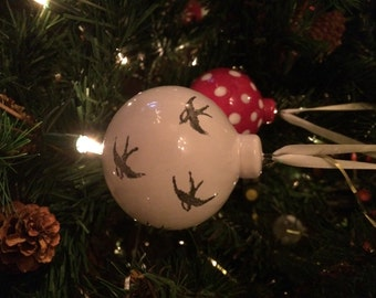 Ornament ceramic bauble: birds, swallows on a white background. Hand painted and glazed ceramic Christmas decoration