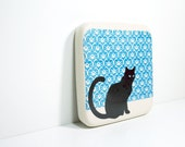 tile with a black cat on an arabesque blue print, ready to go.