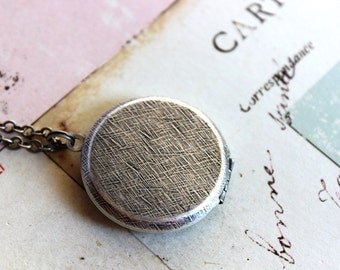 round. locket necklace. silver ox jewelry with etched lines and raised edge front dome back