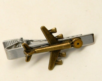 Steampunk jewelry tie tack with airplane and gear.