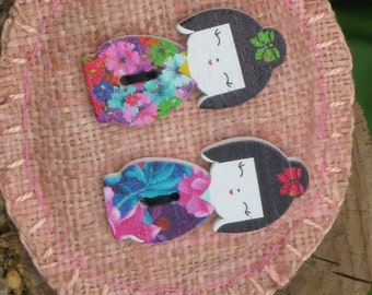Brooch/Pin with wood figures of two Japanease dolls on pink linen background