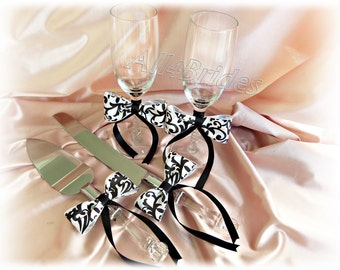 Black and white damask wedding cake knife set and champagne toasting glasses.