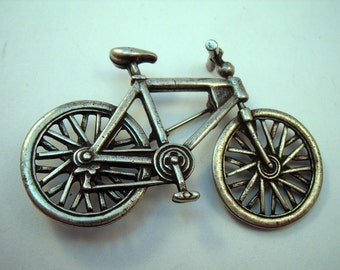 Bicycle brooch with moving wheel