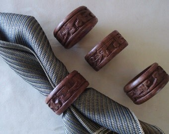 A Set Of 4 Hand Carved Wood Wooden Napkin Rings.