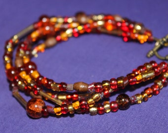 4 Strand Autumn Bracelet in reds, golds and browns.