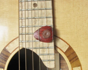 Exotic Padauk wood guitar pick with leather friction pads.