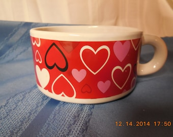 Valentines soup cup, or cappucino cup red with different colored hearts on side.
