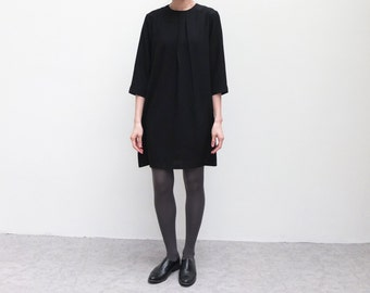 classic black dress with 3/4 sleeve and pleated neckline