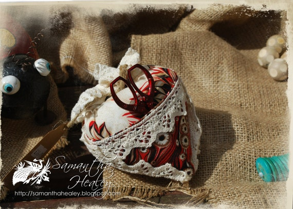 Red and cream fabric pin cushion with small thread scissors