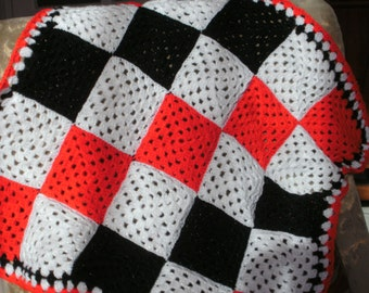 Black, red and white crochet blanket made using granny squares in double knitting