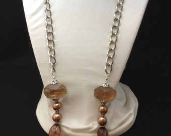 Long, neutral colored beaded necklace with chain
