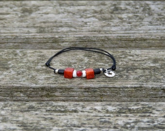 Bracelet with red coral from mediteranean sea, ebony beads, small red sarovski cristal, genuine silver beads on a black adjustable lacing