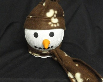 A adorable light up snow person with a brown fleece hat and scarf with paw prints
